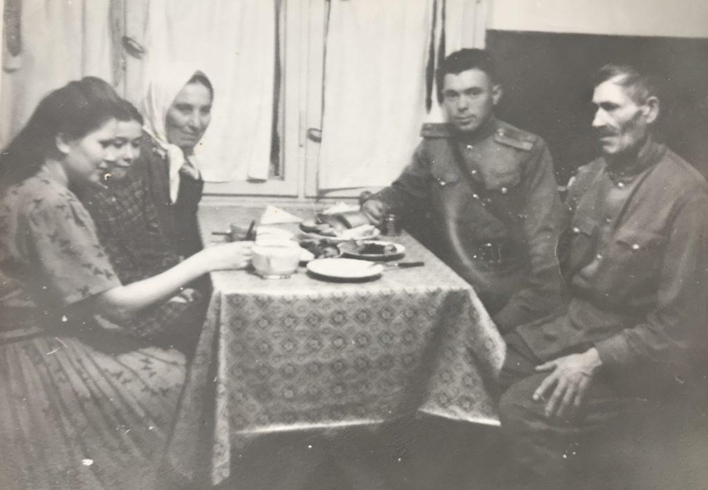 Акулина Климентьевна Кудинова (слева у окна) с невесткой Евстолией Максимовной, внучкой Валей и мужем Тихоном Ивановичем (крайний справа). Калининград, 1950-е